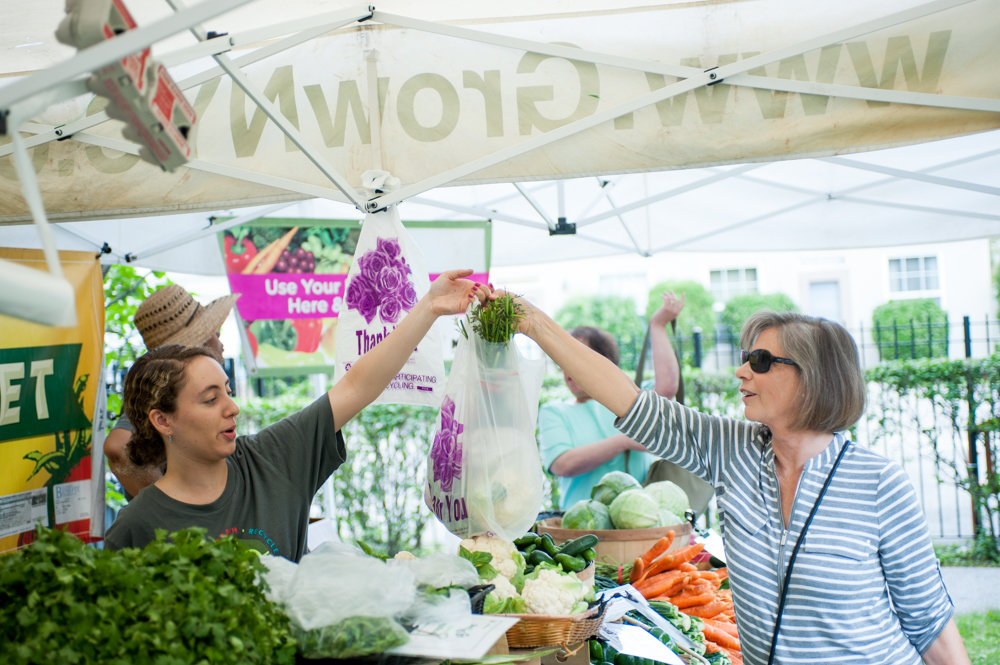 Fiona Hernandez hands a customer her bag of vegetables at the Youth Market at the Riverdale Neighborhood House in 2017. City council Speaker Corey Johnson says he understands the appeal of fresh produce, and has created an interactive 'farm-to-city' map that highlights more than 300 locations citywide where people can find fresh, healthy food.