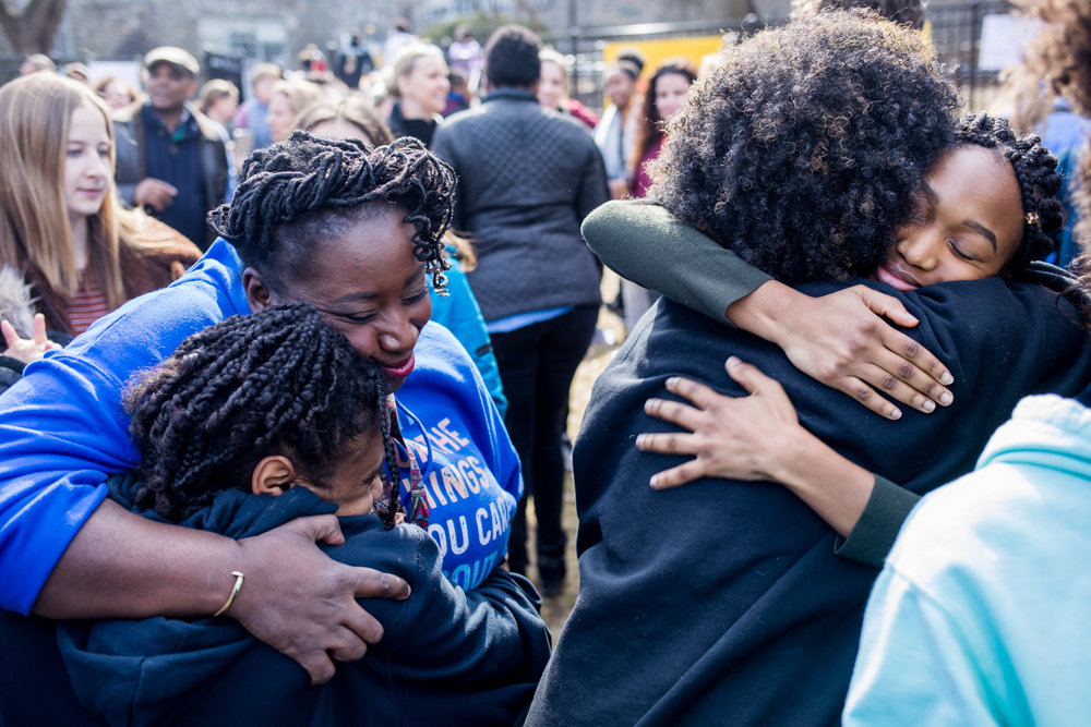 People hug each other after a press conference focusing on students pushing for reform from the administration at Ethical Culture Fieldston School. The gathering followed a student-led multi-day occupation of the school's administrative building, where they demanded administrators take stronger steps toward combating racism at the school.