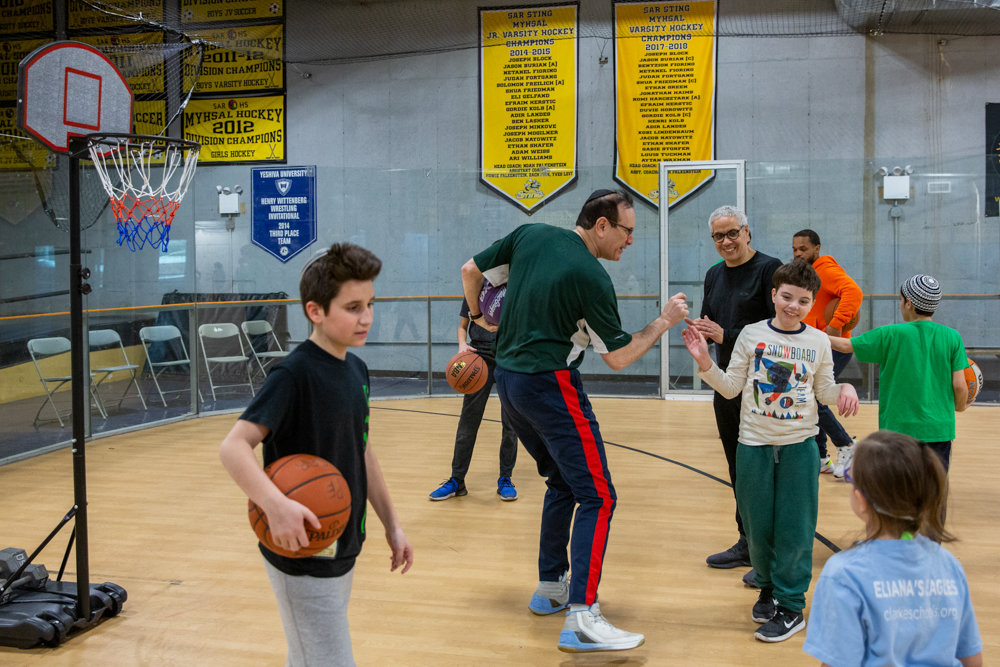 David Shapiro, holding a basketball at left, and volunteer Harold Brem, center, are part of a unique program called Inclusion Basketball, which benefits children with disabilities.