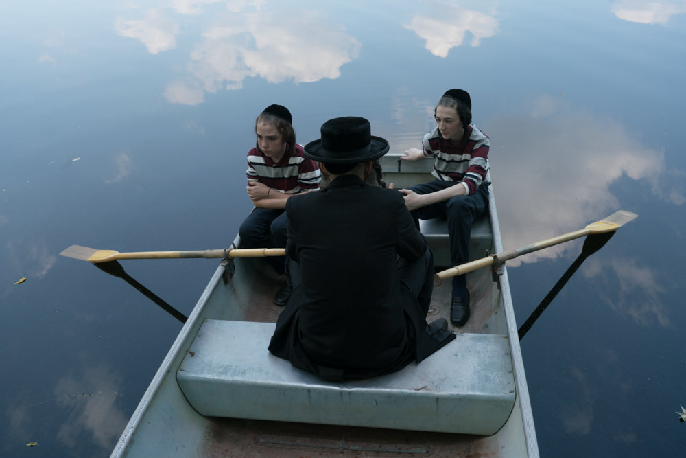 Sammy Voit, left, sits in a boat with fellow young actor Leo Heller in a scene from the independent film 'To Dust,' which features Matthew Broderick. The teenager is balancing time between Los Angeles and Riverdale as he pursues an acting career.