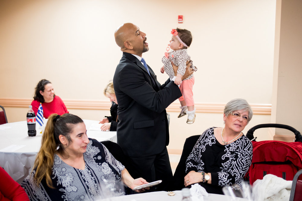Bronx borough president Ruben Diaz Jr., at an evening celebrating Greek heritage, holds a baby in St. Peter the Apostle Greek Orthodox Church.