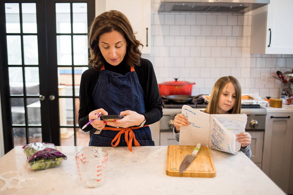 Lea Geller, left, checks a recipe on her phone while her daughter Sidney checks a handwritten recipe in their North Riverdale Home. Geller is the author of 'Trophy Life,' a comedic novel inspired by the trophy wives she knew when she and her family lived in California. It was published April 9.