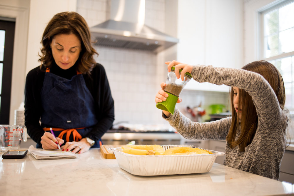Lea Geller checks a recipe while her daughter Sidney grinds pepper over a tray filled with squash. Geller drew inspiration from her time living among trophy wives in California for her debut novel 'Trophy Life,' published April 9.