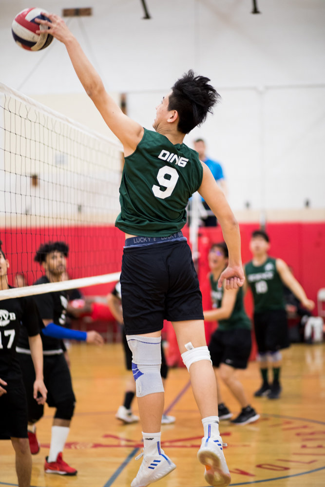 Bronx Science junior Noah Ding goes up for one of his two blocks in the Wolverines' straight-set victory over Clinton.