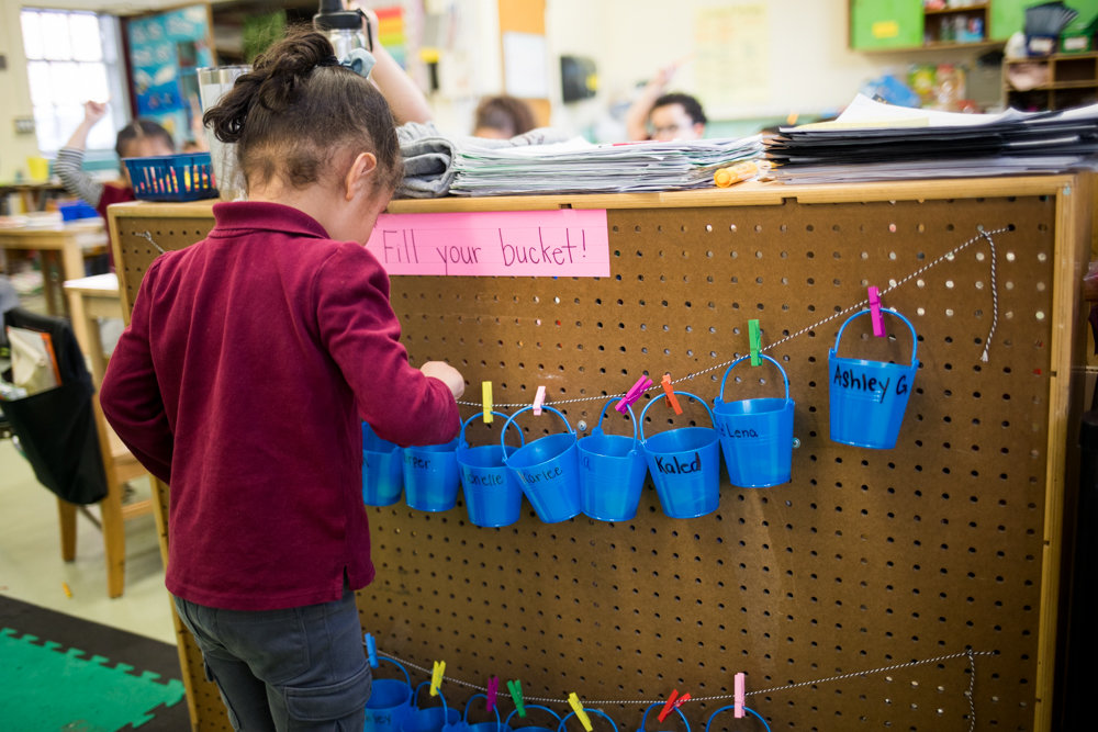 A student in Samantha Scoca's P.S. 7 kindergarten class drops a counter in her bucket during a lesson. The school instituted a new curriculum geared toward students' social and emotional well-being. Part of that is positive reinforcement of good behavior, rather than punishment for bad behavior. In classes like Scoca's, students drop counters in their buckets for doing something good.