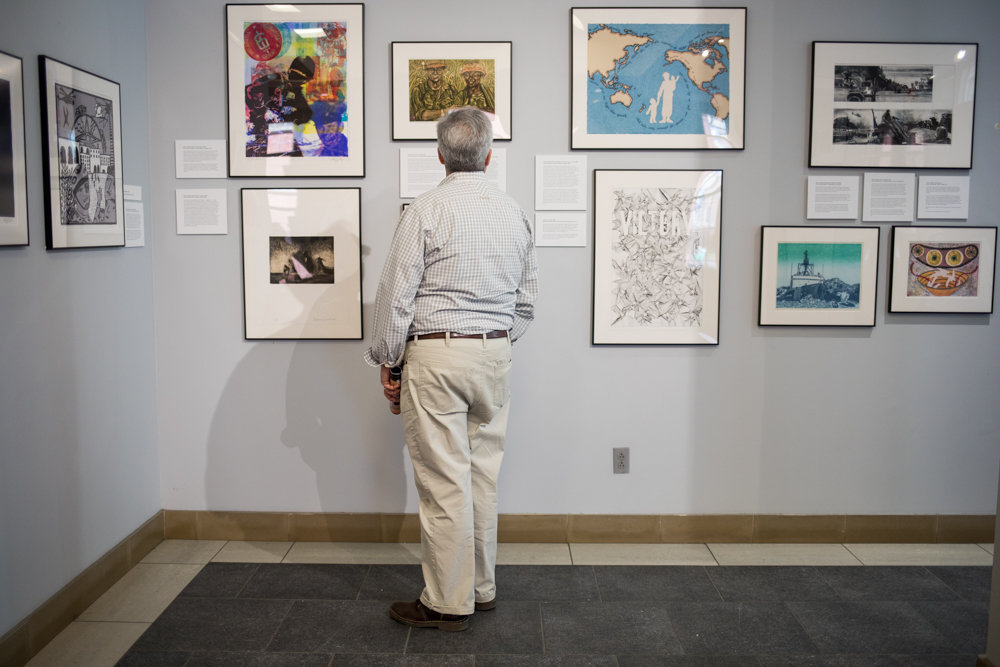A visitor looks at artwork in 'Experiencing Veterans and Artists Collaboration,' an exhibition on display at Manhattan College's O'Malley Library through June 21.