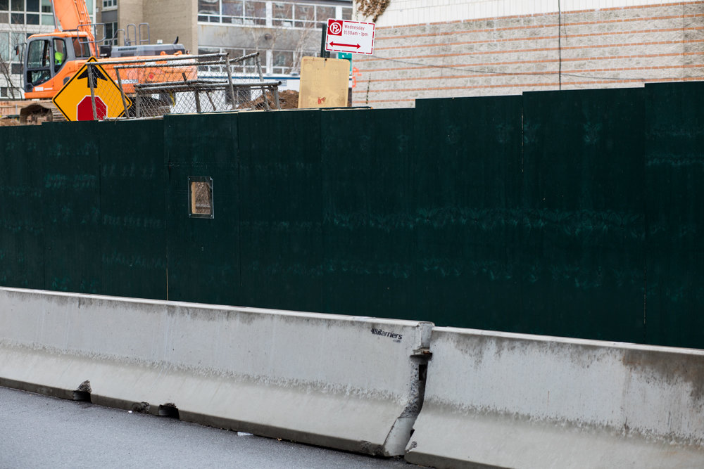 A green construction barrier mostly obscures a parking regulation sign outside 3707 Blackstone Ave. The work has blocked off just about every parking spot adjacent to the corner lot at West 237th Street and Blackstone. Assemblyman Jeffrey Dinowitz — who lives across the street — isn't happy about it.