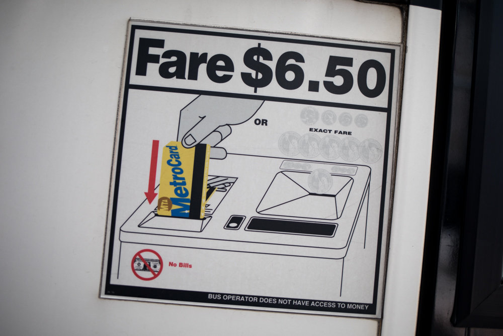 A sign posted on the side of an express bus shows the fare amount and forms of payment — a MetroCard or the amount in coins. As part of an MTA initiative to improve service, express buses no longer accept coins.
