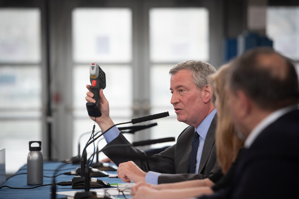 Mayor Bill de Blasio holds up an X-ray fluorescence analyzer as he announces lead-based paint testing at 135,000 NYCHA apartments during a press conference at the Williamsburg Community Center in Brooklyn. The analyzer will help officials more easily detect lead in NYCHA facilities, according to the mayor's office.