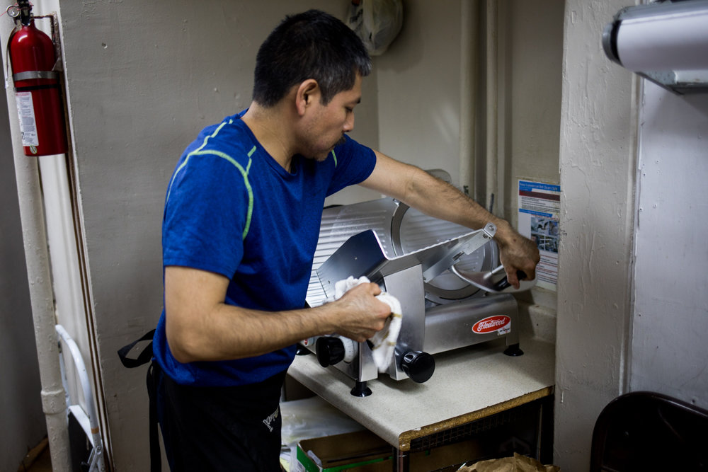 Josue Guerrero, owner of Yohan's Deli & Grocery, wipes down a slicer. During slower months, Guerrero feels the heat when it comes time to paying rent, which is a shared concern among immigrant business owners, according to a recent study.