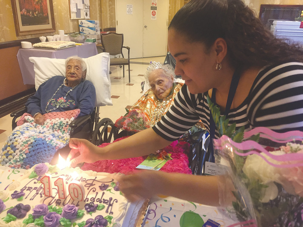 Bernice King dons a tiara with a shiny gold and red shawl as she watches the candles lit for her 110th birthday cake at Manhattanville Health Care Center in 2017. King died March 28, just a week short of her 112th birthday.