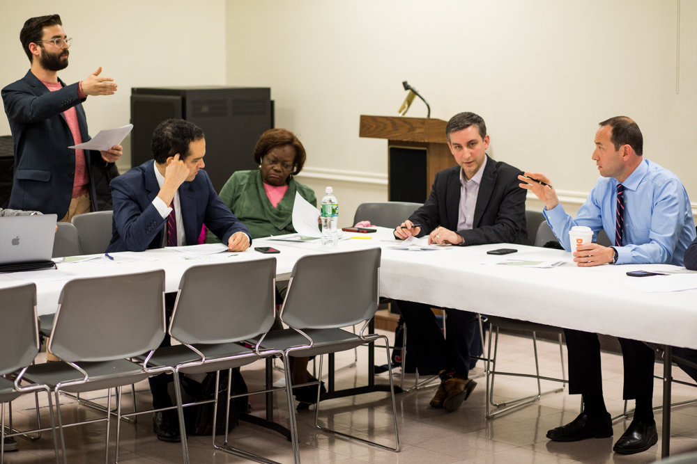 CB8 member Dan Padernacht, right, seeks clarification from Timber Equities spokesman Sam Spokony, at far left, during a land use committee meeting Monday night. Spokony represents Timber Equities, which wants to build a four-story apartment building at 3893 Waldo Ave.