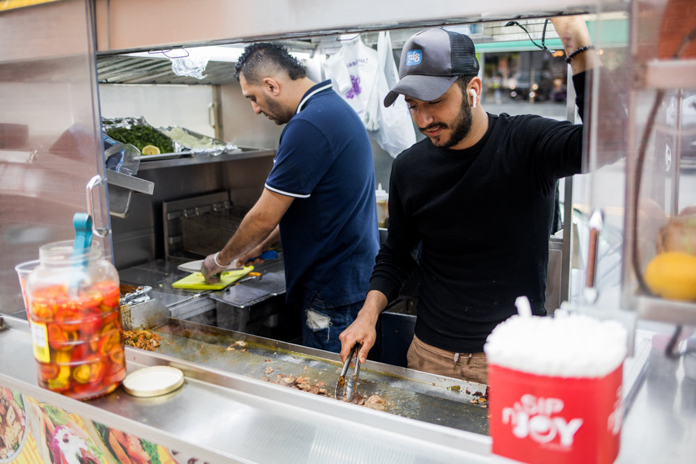 Karim Sokar, right, and Mamdouh Ibrahim prepare food on a Johnson Avenue cart.