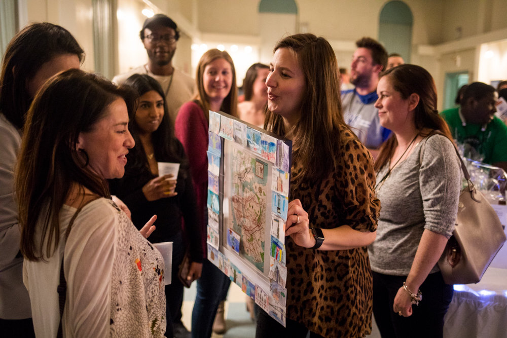 Audrey Routliffe displays a student-made artwork up for bid during an auction at the AmPark Neighborhood School's annual fundraiser at the Amalgamated's Vladeck Hall.