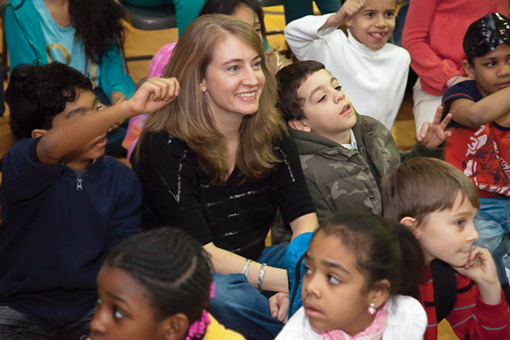 Sadie Mahoney, director of youth services at the Kingsbridge Heights Community Center, sits with students in the center's after-school program in 2012. Mahoney is not thrilled about the mayor's proposed cuts to the School's Out NYC program, which funds summer camp activities — including KHCC's — citywide.