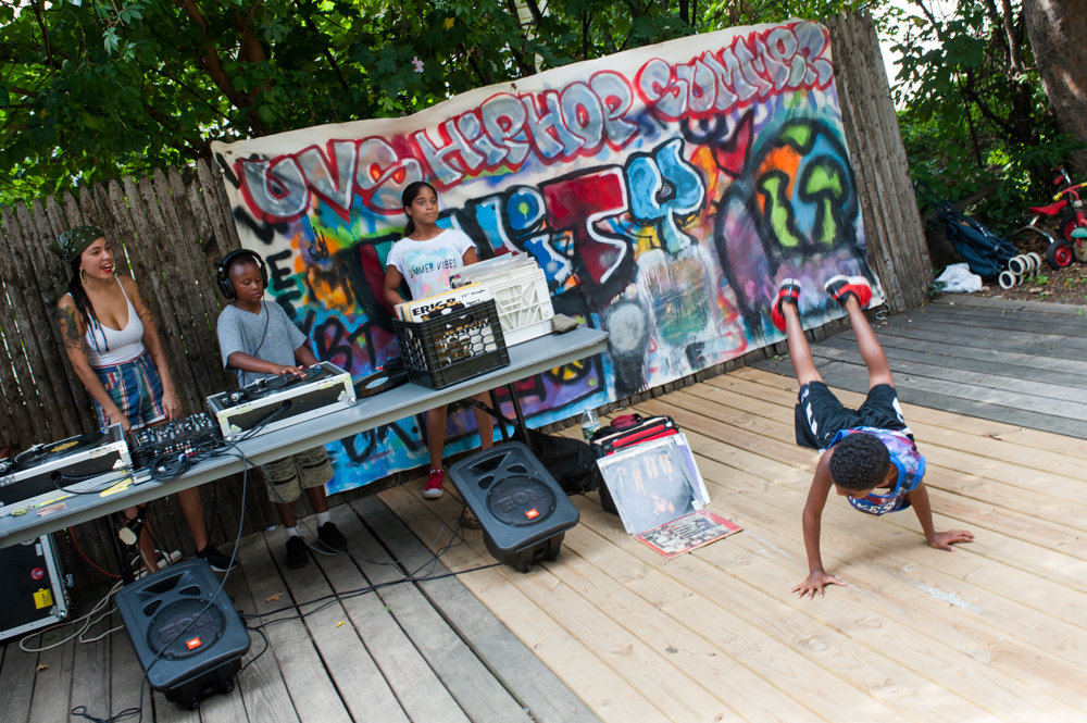 Maximo Reyes, breakdances at the Kingsbridge Heights Community Center on the last day of Hip-Hop Summer School in 2017 while Jeremiah David spins the turntable. KHCC is pushing back against proposed cuts to the School's Out NYC program, which funds summer camp activities across the city.