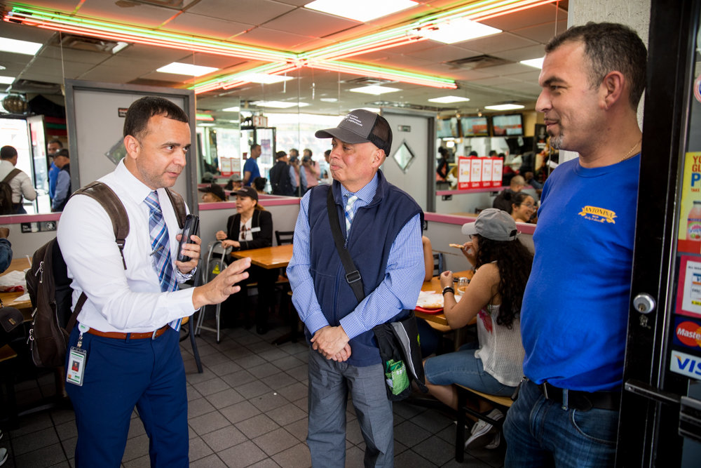 Angel Pagan, compliance advisor for the city's small business services agency, left, tells Broadway Pizza & Pasta owner John Kambouris what he needs to know about new regulations to ensure his business is in compliance.