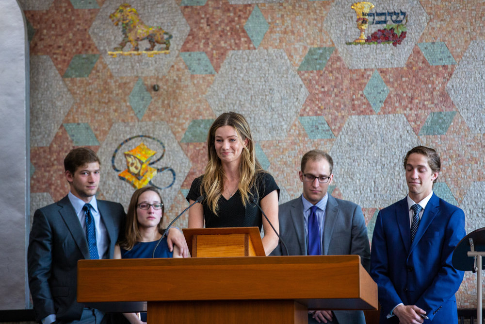 Alexandra Sonett reads 'The Golden Woman,' a poem written by her brother Zachary, during a memorial service for her grandmother, Judith Sonett, at the Riverdale Temple. Her other grandchildren, Cole, left, Caroline, Jarrod and Judson, right, stand behind Alexandra.