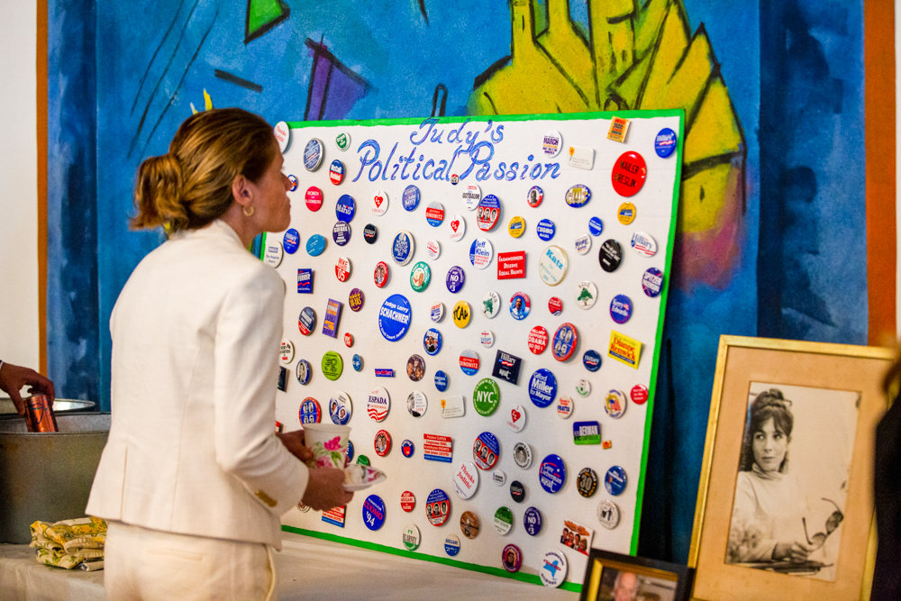 An attendee of a memorial service for artist and political activist Judith Sonett looks at a board full of Sonett's pins at the Riverdale Temple.