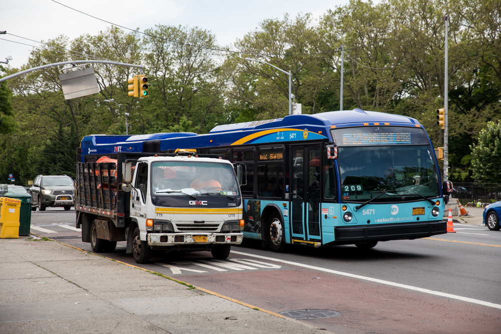 A Bx12 bus navigates around a truck idling in the bus lane on West Fordham Road. The city's transportation department wants to install bus lanes like this on Broadway between West 225th and West 230th streets in Marble Hill.