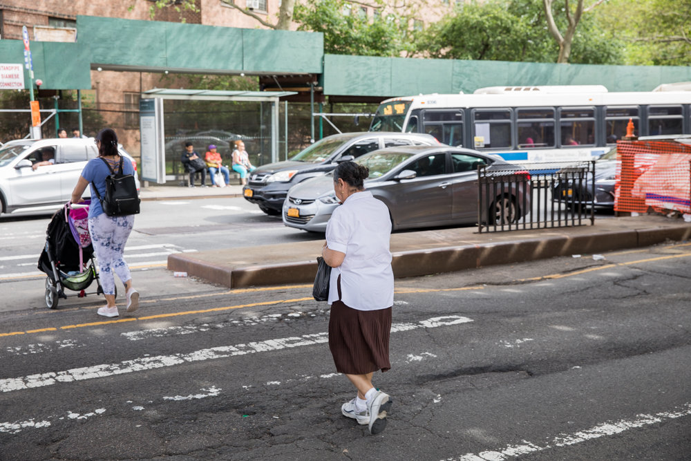 Pedestrians cross Broadway at West 230th Street while a Bx20 bus pulls to a stop. The city's transportation department wants to install bus lanes on Broadway between West 225th and West 230th streets.
