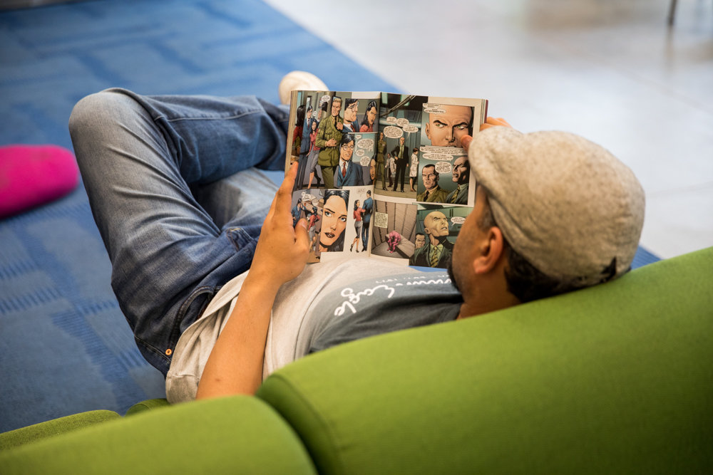 A library patron reads a comic book in the Kingsbridge Library. Next year's city budget includes a proposed $10.4 million cut to library funding, which could affect the programs available at branches like Kingsbridge.