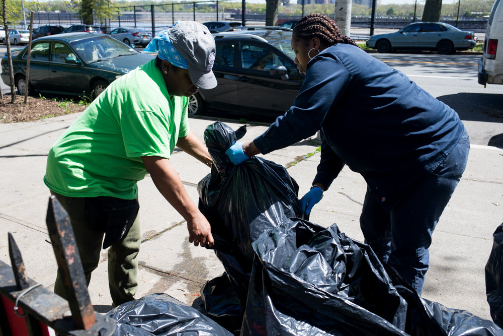 Kathy Rodriguez, left, and Kim Ryer clean up trash at Fort Four Park. Joel Guerrero has used the park since he was a kid, and now wants to give back by working to revamp the basketball courts there.