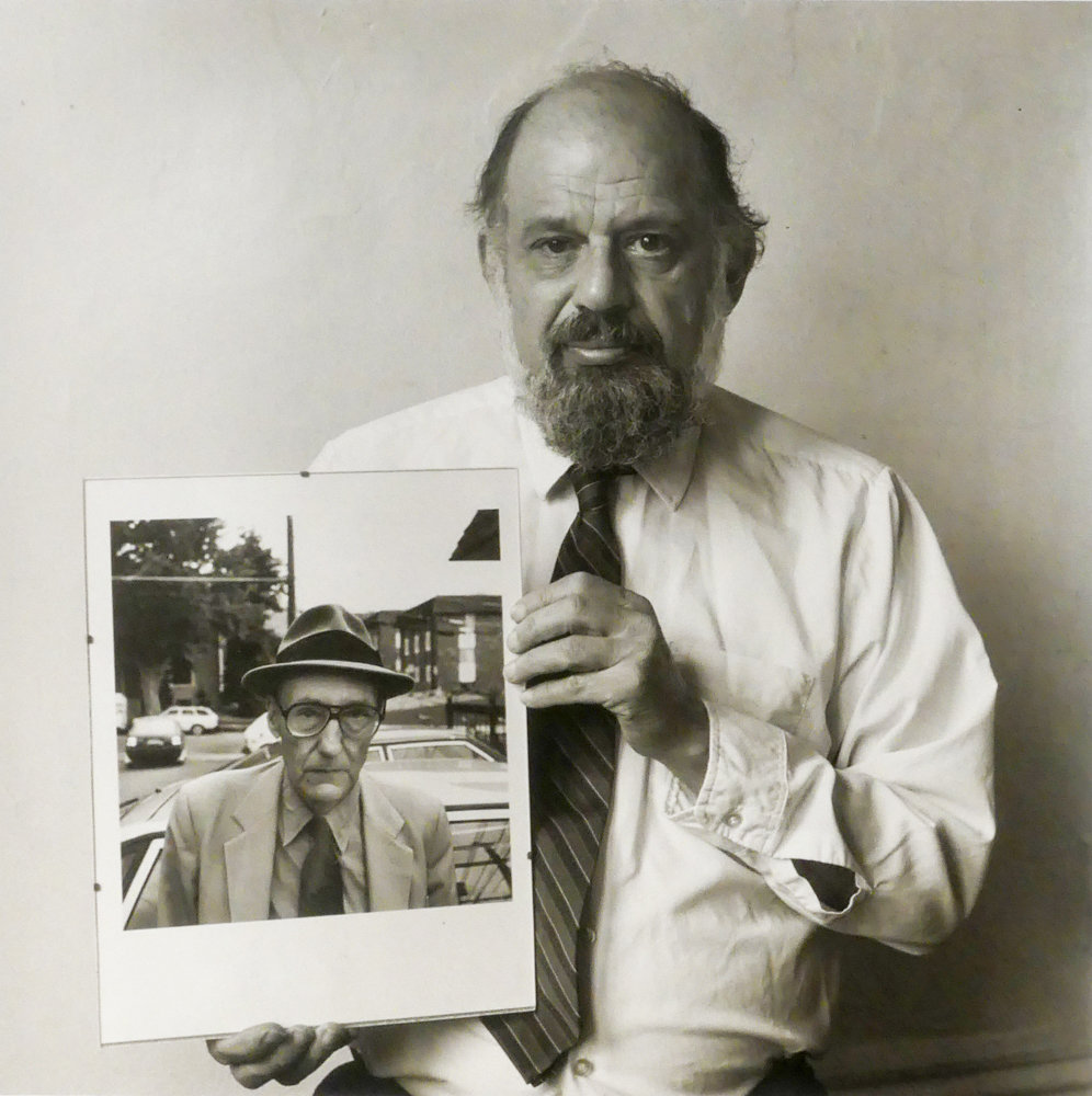 Poet Allen Ginsberg holds a photograph he took of writer William S. Burroughs in a 1986 portrait by Robert Giard. This photograph is included in the exhibition 'Particular Voices,' on display at Daniel Cooney Fine Art through July 26.