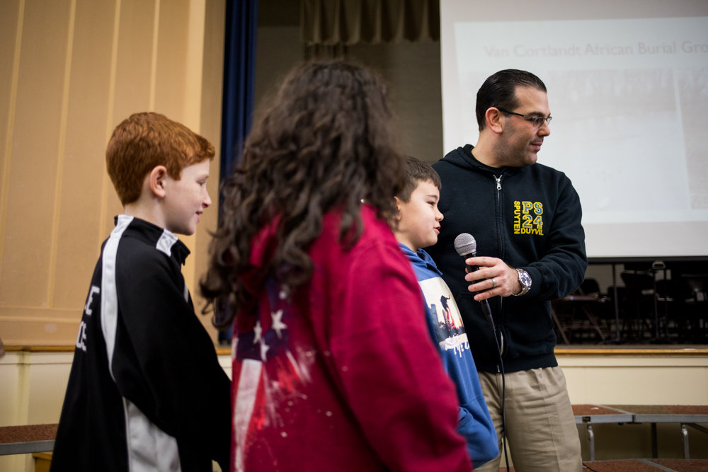 P.S. 24 principal Steven Schwartz holds the microphone for a student during a presentation about African American history in February. A recent anonymous email campaign alleged Schwartz tweeted about gambling on horse racing during school hours.