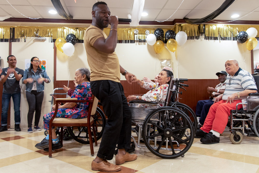 James Ramsey of the Every Thing Covered Band sings and dances with residents from the Park Gardens Rehab & Nursing Center for the second annual Senior/Senior Prom, featuring students from Marble Hill High School for International Studies.