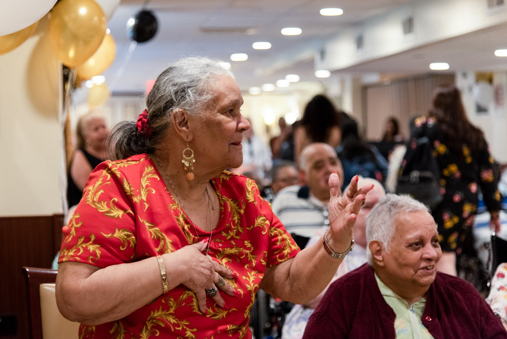 Dorca Rodriguez stands up to sing and dance a salsa song during the Senior/Senior Prom at the Park Gardens Rehab & Nursing Center, which brought together center residents and Marble Hill High School seniors.