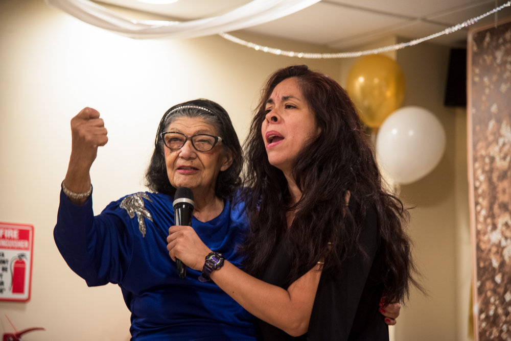 Benedicta Torres, left, a resident of Park Gardens Rehab & Nursing Center, sings with Cynthia Feliciano from the Every Thing Covered Band at the center's Senior/Senior Prom. The second annual event brought together center residents and Marble Hill High School seniors.