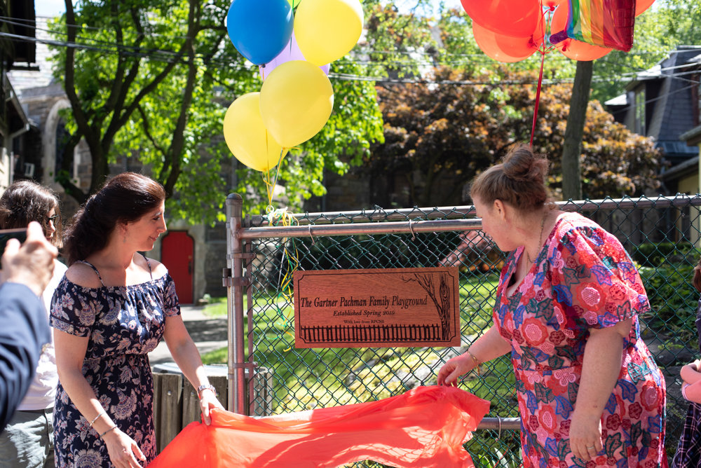 Jodi Pachman, right, and Riverdale Presbyterian Church Nursery School director Lauren Mactas, unveil the plaque for the Gartner Pachman Family Playground during a recent dedication ceremony.