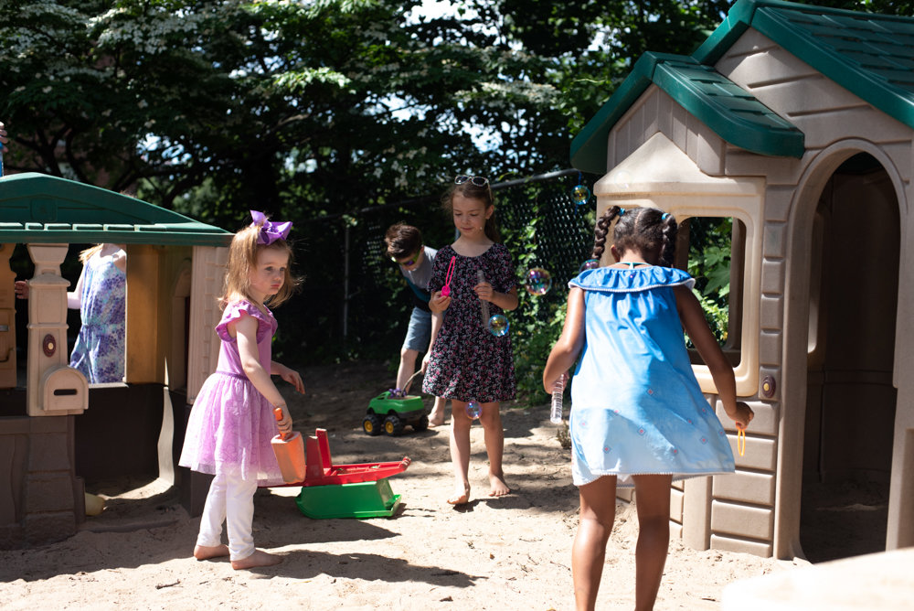 Children enjoy the playhouses in the Gartner Pachman Family Playground, the newly dedicated recreation area at the Riverdale Presbyterian Church Nursery School on Henry Hudson Parkway.