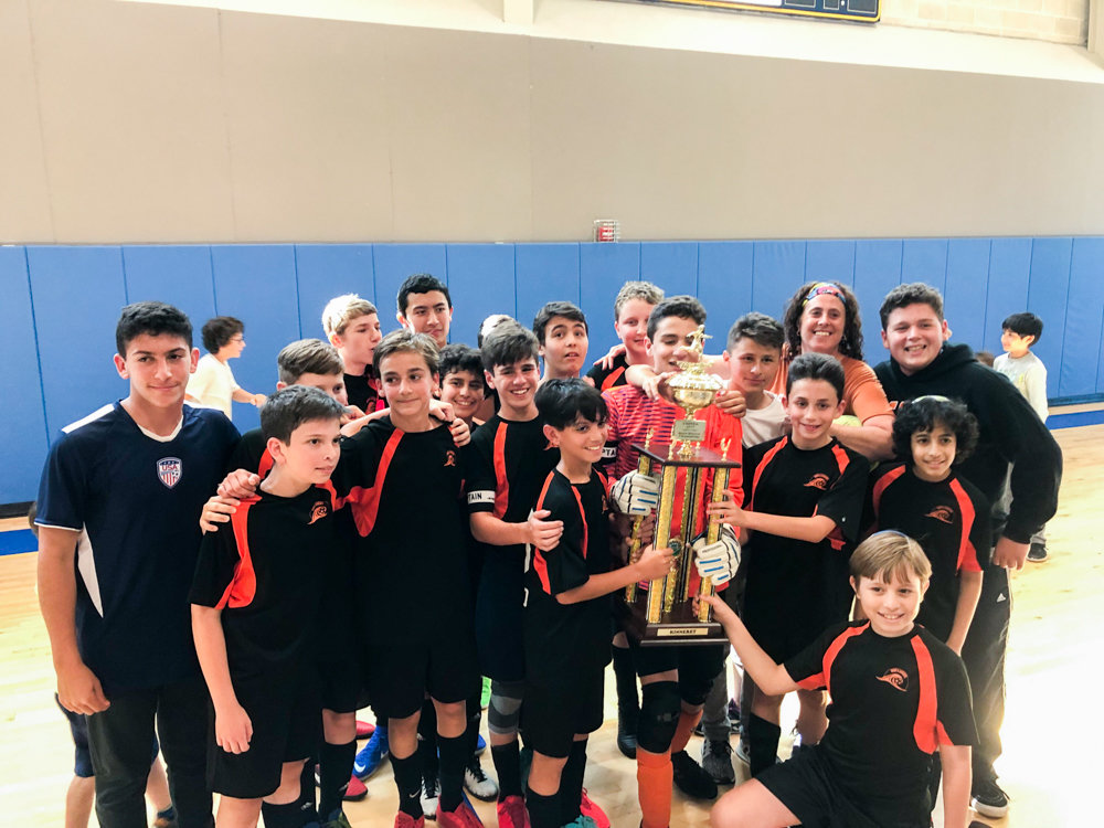Coach Allison Horn, back right, and her Kinneret Day School boys soccer team celebrate their championship after a 4-1 victory over The Moriah School.