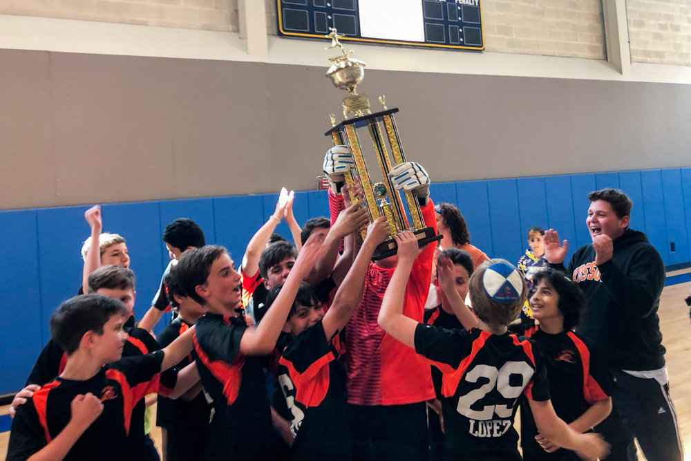 The scoreboard in the background tells the story as the Kinneret Day School boys soccer team hoists its championship trophy last week.