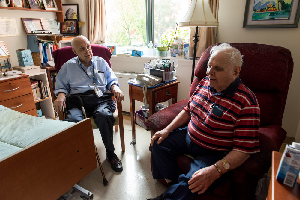 Jerry Schneider, a 92-year-old volunteer at the Hebrew Home at Riverdale, left, visits his 87-year-old friend David Oscar. Schneider reads newspapers and books to Oscar, who has problems seeing.