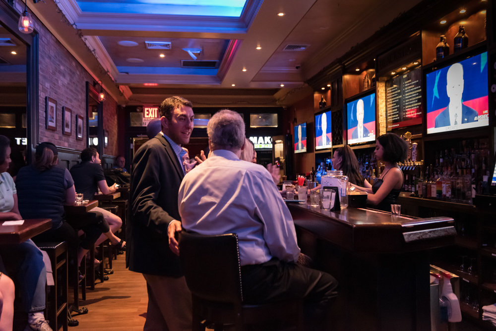 City council candidate Eric Dinowitz speaks with his father, Assemblyman Jeffrey Dinowitz, during a watch party for the second night of the Democratic presidential debate hosted by the Benjamin Franklin Reform Democratic Club at Blackstone Bar & Grill.