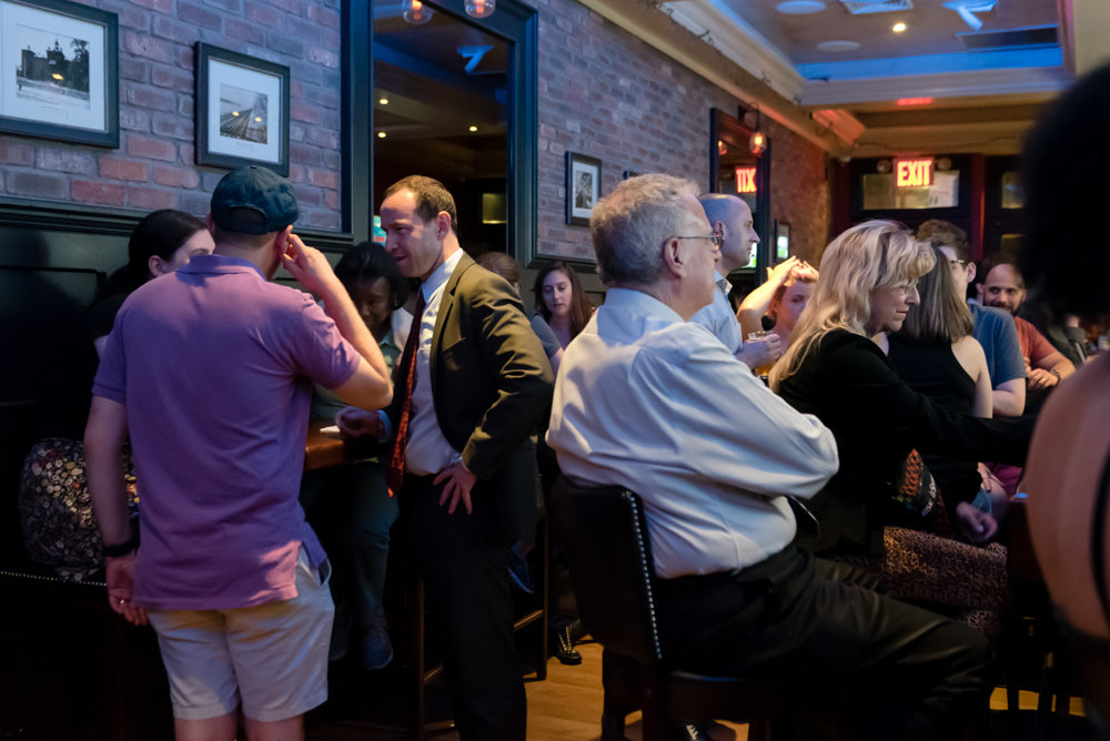 City council candidate Dan Padernacht, second from left, talks with Benjamin Franklin Reform Democratic Club member Aaron Stayman during a watch party for the second night of the Democratic presidential debate hosted at Blackstone Bar & Grill on Riverdale Avenue.