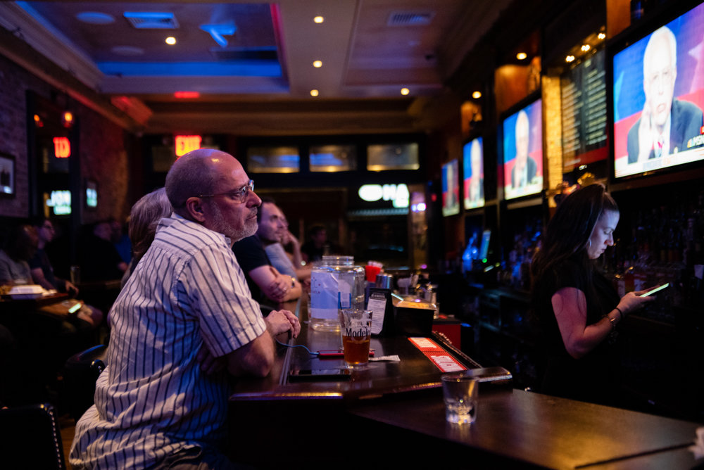 Andrew Mutnick, former chief of staff for state Sen. Alessandra Biaggi, watches the second night of the Democratic presidential debate at a watch party organized by the Benjamin Franklin Reform Democratic Club at Blackstone Bar & Grill.