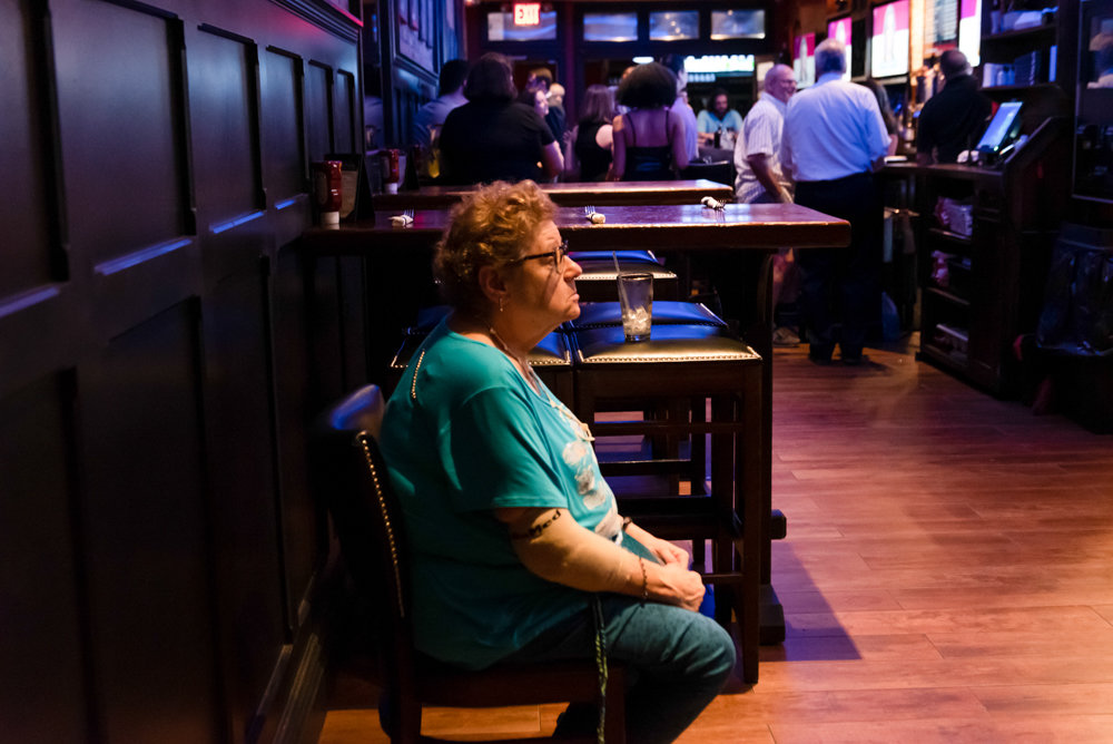 In a bid for some peace and quiet to watch the second night of the Democratic presidential debate, Merrit Claude sat at the back of Blackstone Bar & Grill on Riverdale Avenue during a debate watch party hosted by the Benjamin Franklin Reform Democratic Club.