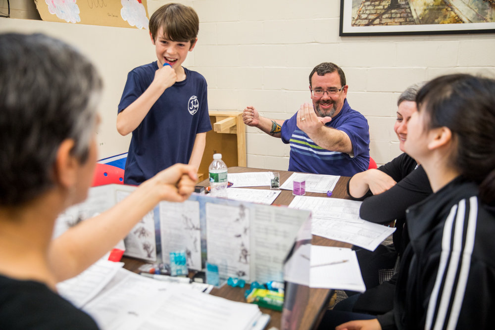 Dungeons and Dragons player Josh Soule, center, faces off with dungeon master Lara Dua-Swartz, far left, in a battle sequence as Liam Belton looks on. A boisterous group of players gather for gaming sessions at the Spuyten Duyvil Library every Thursday.