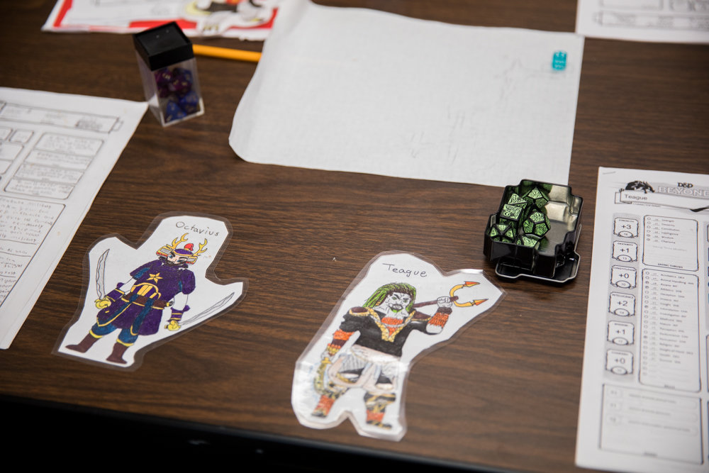 Character drawings and multi-sided dice sit on a table during a Dungeons and Dragons campaign at the Spuyten Duyvil Library.