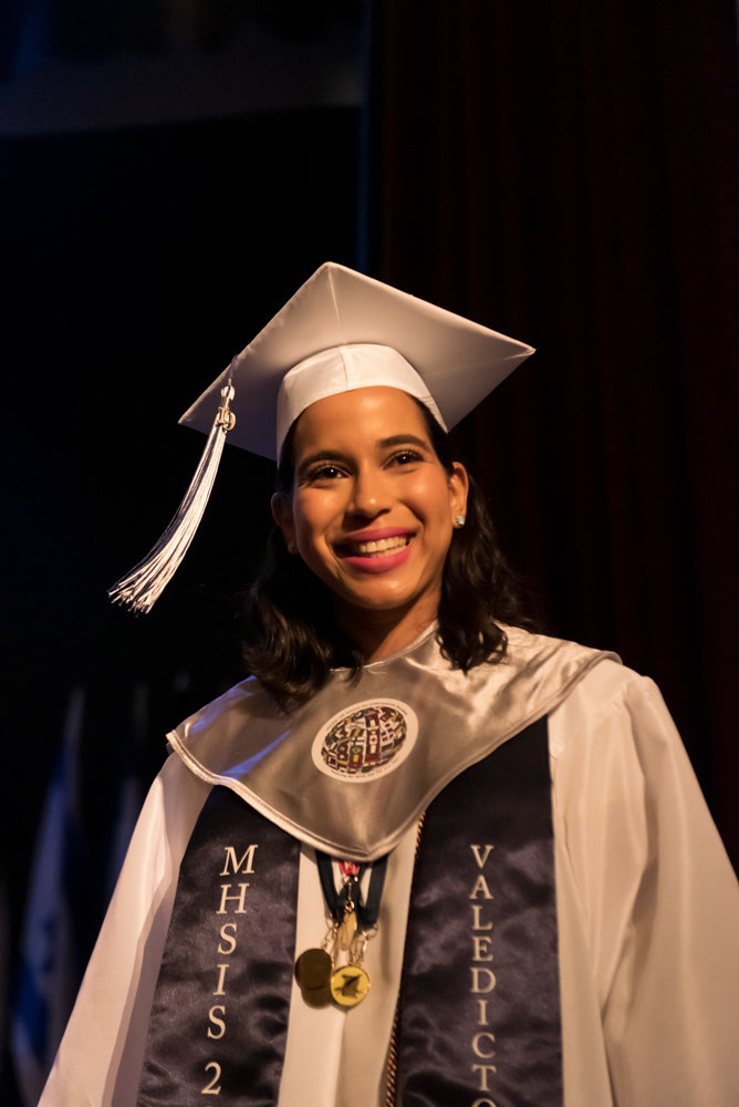 Angela Veras Oriach smiles as she leaves the stage after receiving an award during the graduation ceremony of Marble Hill High School for International Studies. Oriach was her class valedictorian.