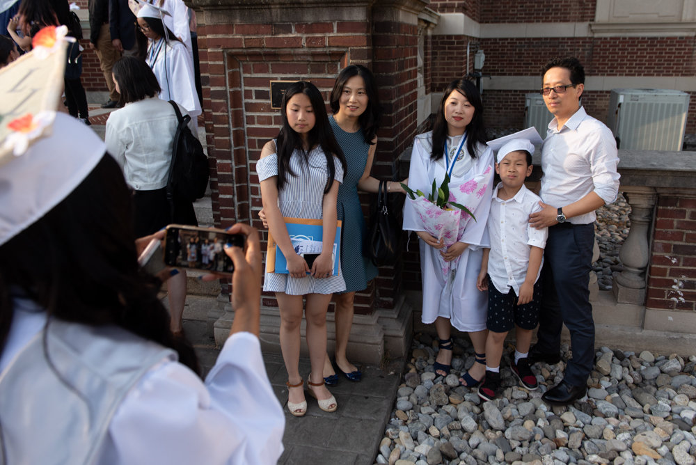 Graduates of Marble Hill School for International Studies take pictures with loved ones after their graduation ceremony at the College of Mount Saint Vincent.
