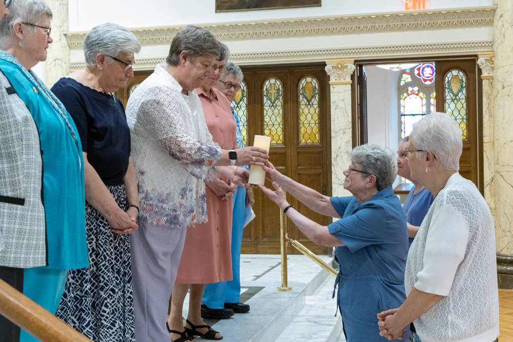 Former Sisters of Charity president Sister Jane Iannucelli, center right, presents a candle to the organization's new president, Sister Donna Dodge.