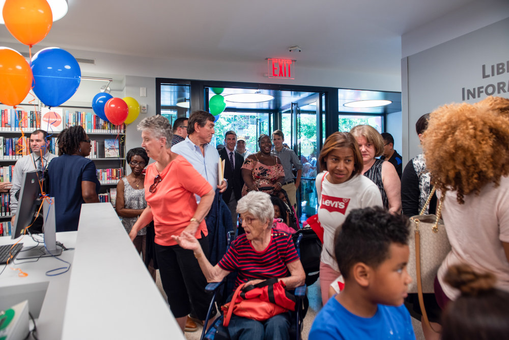 People walk into the new 3882 Cannon Place location for the Van Cortlandt Library after a ribbon cutting ceremony Monday.
