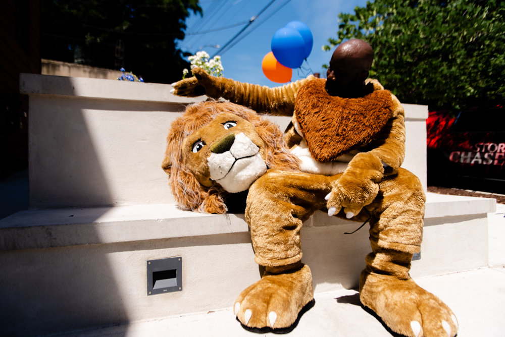 Cyprian Johnson takes a moment to get some fresh air after the ribbon-cutting ceremony for Van Cortlandt Library's new location at 3882 Cannon Place. Johnson dressed as Patience, the New York Public Library's lion mascot.