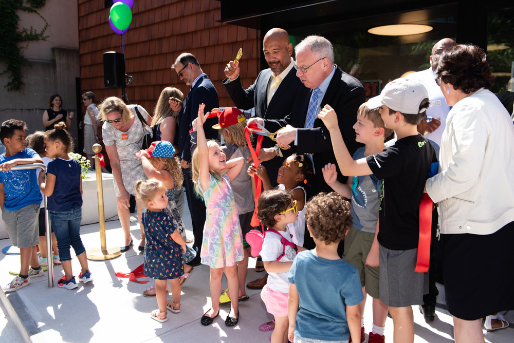 Children surround elected officials and library staff members after the ribbon-cutting ceremony for the Van Cortlandt Library's new location at 3882 Cannon Place.