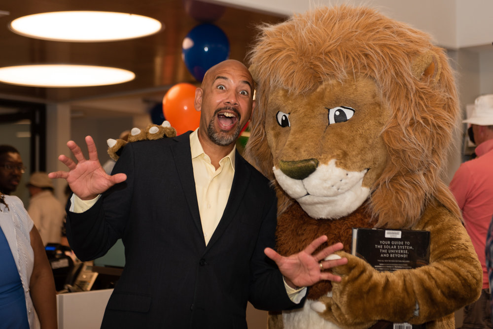 Bronx borough president Ruben Diaz Jr., alongside the New York Public Library's mascot Patience, does his best lion impersonation inside the new location for the Van Cortlandt branch.